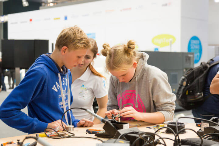 A highlight at the Youth Education and Development Foundation's special booth for youth is a process chain from the drawing up to as-sembly of a Formula 1 model car. Young visitors concentrate on their work building this model.
