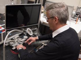 LaFT-Leiter Jens P. Wulfsberg demonstriert an einer Vorschubeinheit für Mini-2D-Werkzeugmaschinen, wie Armstütze aus dem 3D-Drucker den Monteur bei der Arbeit unterstützen. Exoskelette sollen die Arbeitssicherheit erhöhen.