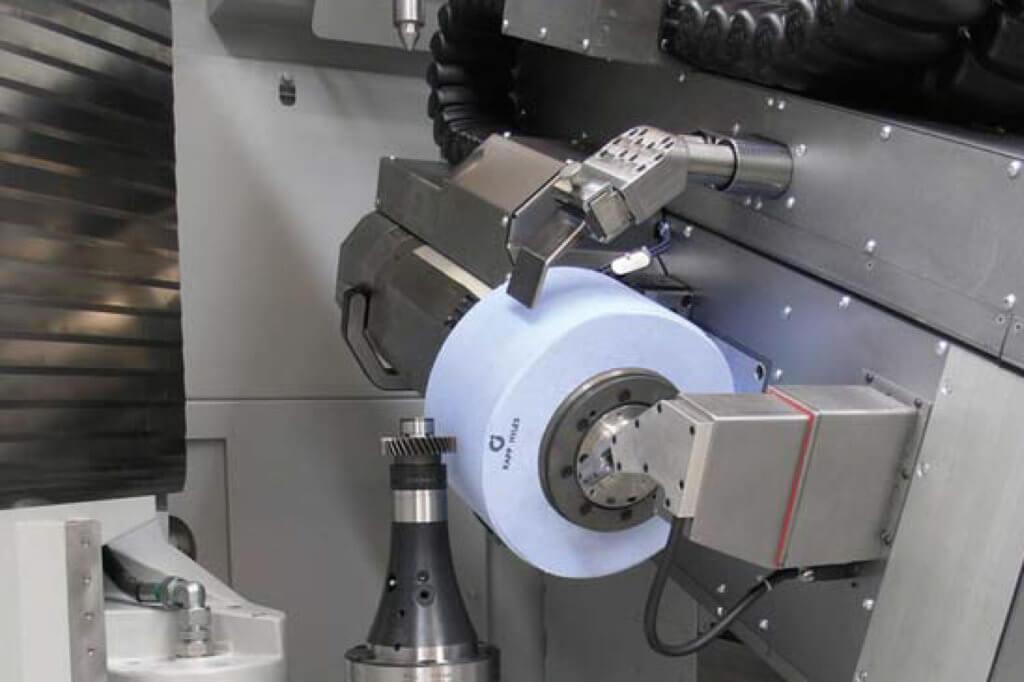 Arbeitsraum einer Verzahnungsschleifmaschine: In den großen Schleifwerkzeugen beispielsweise für das Wälzschleifen können sehr große Rotationsenergien stecken, die bei Bruch des Schleifkörpers schwerste Verletzungen der Maschinen-bediener hervorrufen könnten. Foto: Kapp